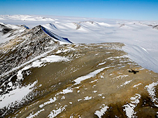 NASA's DC-8 casts its shadow on a ridgeline of the Shackleton Range.