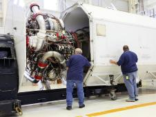 Technicians oversee the installation of a Pratt Whitney Rocketdyne RS 25D engine into a transportation canister.
