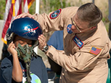 NASA Dryden research pilot Mark Pestana demonstrated a helmet and oxygen mask worn by pilots of high-performance aircraft to a student.
