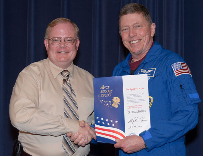 NASA astronaut Mike Fossum congratulates Dryden flight surgeon Dr. Gregg Bendrick as he presents a Silver Snoopy Award to Bendrick for his support of the space shuttle program.