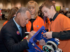 NASA administrator Charlie Bolden autographs part of the Lancaster High Eagle Robotics team's 2012 X-1 robot held by team member John Graham prior to Bolden's address at the Antelope Valley Board of Trade's Business Outlook Conference Feb. 24.