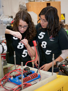 Tehachapi High Cyber Penguins electronics team members Jessica Burke and Jessica Medina check out wiring on their 2012 robot during rollout.