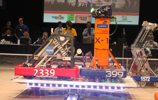Robots from Antelope Valley (2339) and Lancaster (399) high schools team up at the San Diego regional competition to balance on the tilting bridge.