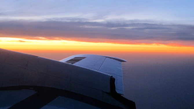 Looking from the P-3B aircraft window, the sun breaks the morning darkness with a glow on the horizon.