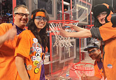 Team mentor David Voracek and Eagle Robotics team members Jackie Patton, John Graham and Christian Pereira (bottom) cut the net after winning the Colorado FIRST Robotics regional games.