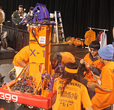 Eagle Robotics team members Jackie Patton, Gabe Ruiz, Kenny Howard, John Graham, and Christian Pereira (behind robot) work to fix a broken actuator on their X-1 robot during the elimination matches.