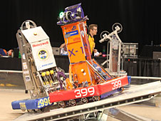 The robots of Lancaster High team 399 and alliance team 2996 work together to balance on the tilting bridge during a qualification match at the FIRST regional in Denver.