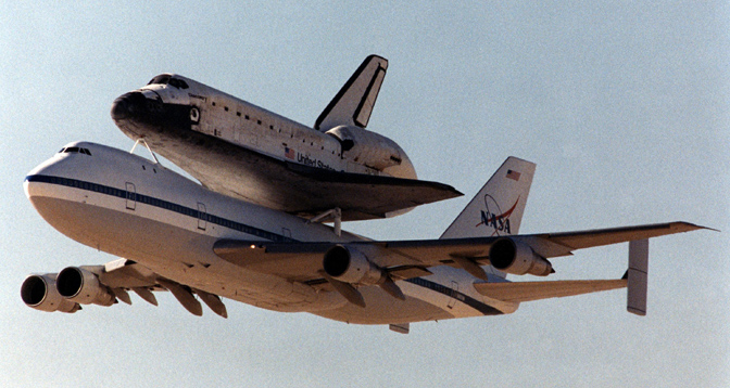 NASA 905, one of NASA's two modified Boeing 747 Shuttle Carrier Aircraft, climbs out after takeoff from Edwards Air Force Base, Calif., on Nov. 2, 2000 with the space shuttle orbiter Discovery on its back.