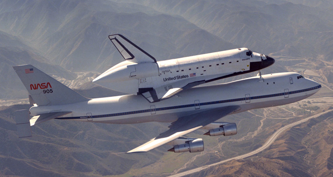 Space Shuttle Discovery rides atop NASA 905, one of NASA's two modified Boeing 747 Shuttle Carrier Aircraft, on its delivery flight from California to the Kennedy Space Center in Florida in 1983.