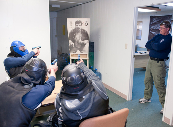 Officers work through a drill where they have to shoot a suspect from a seated position.
