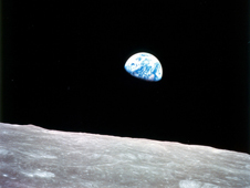 Earthrise - the first ever color picture of the Earth taken from space, hovers blue above a gray moonscape