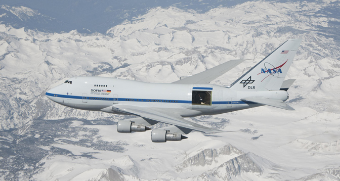 Over a blanket of snow covering California's southern Sierra Nevada mountains, NASA's Stratospheric Observatory for Infrared Astronomy (SOFIA) flies with the sliding door over its telescope cavity fully open.