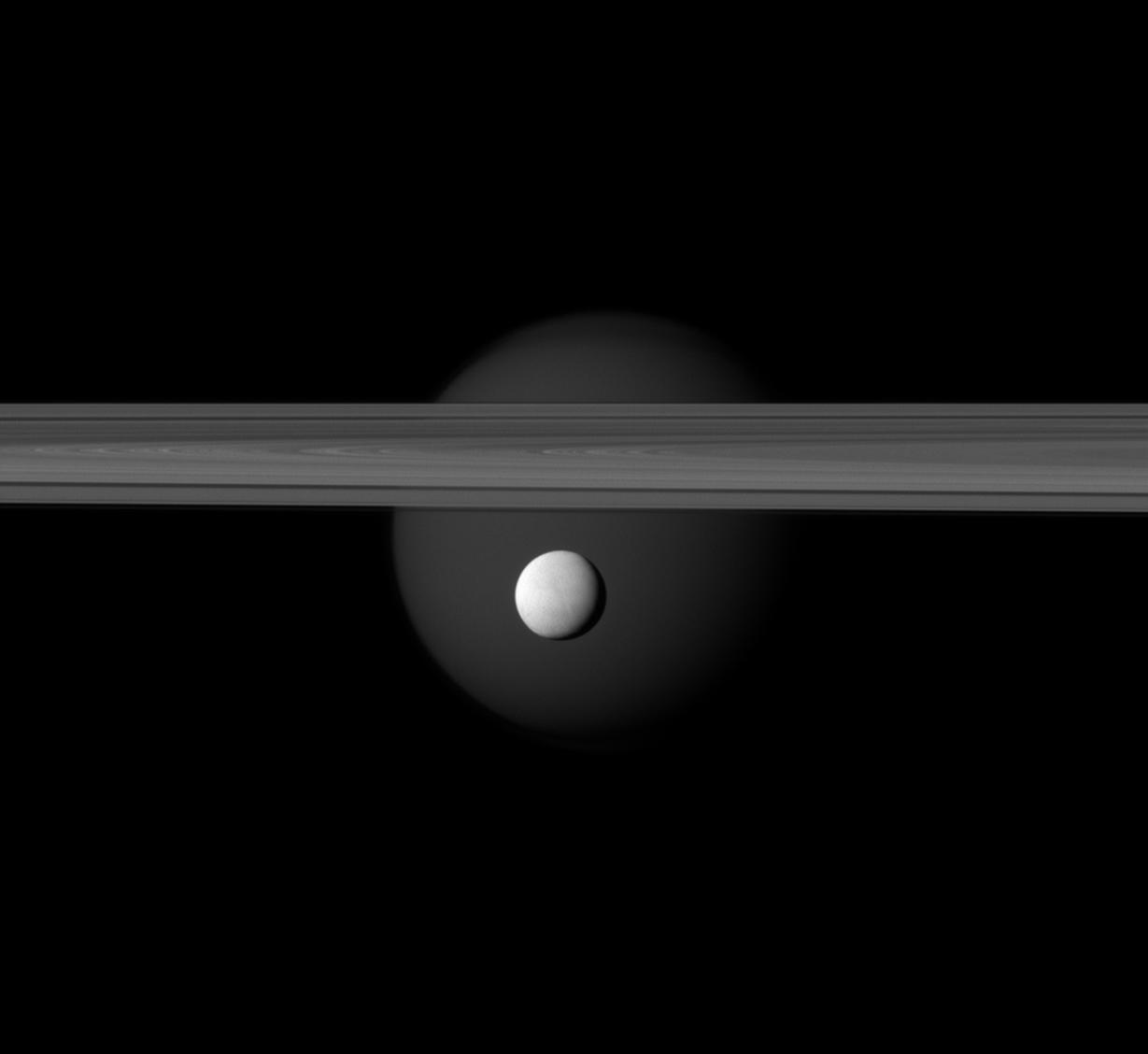 Particolare con il luminoso Encelado in primo piano, gli anelli di Saturno e sullo sfondo Titano. Credits: NASA
