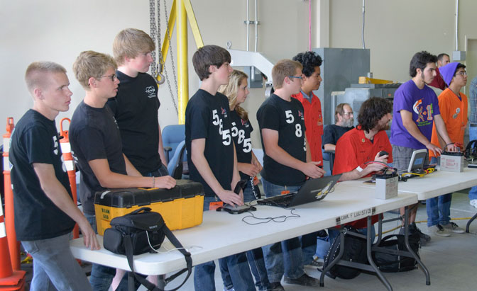 High school robotics teams control their robots.