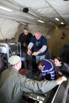 Airborne Topographic Mapper program manager Jim Yungel lifts a floor panel to show the ATM laser altimeter to teachers on an IceBridge flight.