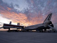 The setting sun provides a beautiful backdrop for Discovery and the Crew Transport Vehicle after Discovery's landing at Edwards Air Force Base on Sept. 11, 2009.