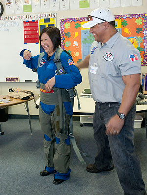 School employee Nancy Pena shows off a high-G flight suit used by NASA pilots.