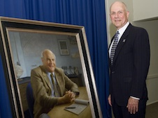 Carl Pilcher standing next to the portrait of Baruch Blumberg.