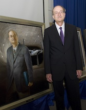 Wayne Johnson standing beside his portrait, which depicts him in the National Full-Scale Aerodynamics Complex.