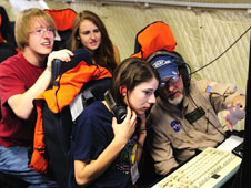 Students watch intently as Dennis Gearhart from NASA Ames and UC-Santa Cruz details data from the MASTER remote sensing instrument on NASA's P-3B Earth sciences aircraft is displayed on a monitor in front of them during a research flight.