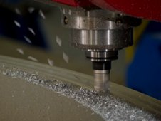 A specialized milling tool grinds away at an aluminum ring at the Marshall Center.