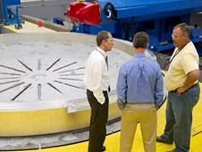 Members of the Space Launch System team discuss the machining of an aluminum adapter ring.