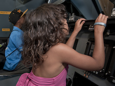 Above a Greene Scholar sits in an aerospace vehicle in the world's largest Vertical Motion Simulator.