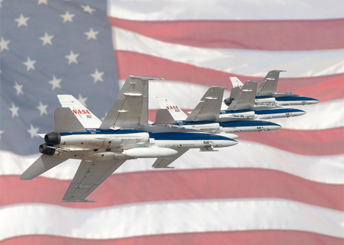 Four Dryden F-18 aircraft flying in formation superimposed over an American flag.