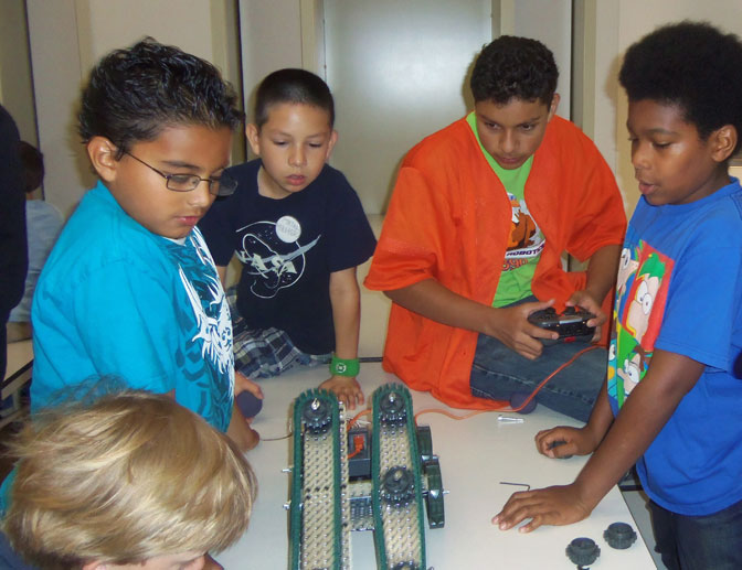 Students check out functions of one of the VEX robots used during the summer robotics workshop.