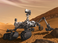 In this artist's concept, the NASA Mars Science Laboratory Curiosity rover examines a rock on Mars with a set of tools at the end of the rover's arm, which extends about seven feet.