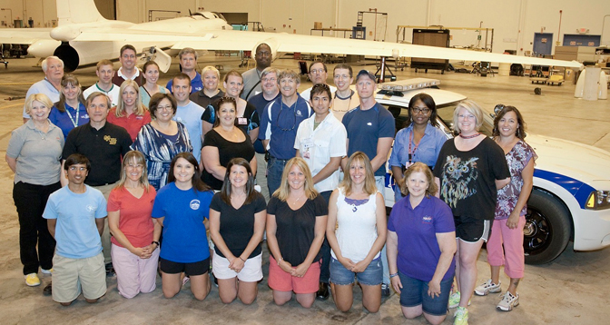 Participants in the two-week AREES workshop gather for a group photo in front of NASA's ER-2 aircraft 806 and its safety chase car.