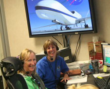 two women in headsets under a monitor showing a global hawk.