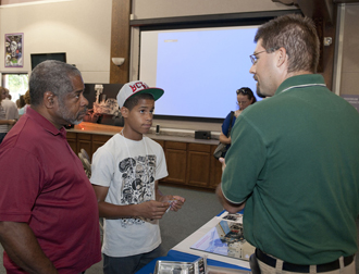 NASA Dryden's Martel Martinez discusses geological aspects of the Curiosity rover's mission on Mars with Gerald and Albert Dummett at the Mars Science Laboratory exhibit in the AERO Institute.