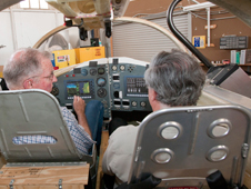 Maj. Gen. Joe Engle sits at a mockup of the Lynx suborbital, reusable launch vehicle with Dan DeLong, XCOR Aerospace vice president and chief engineer.