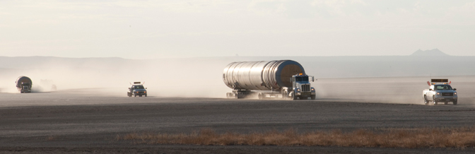 The wheels of the tractor-trailers carrying the two space shuttle solid rocket booster casings and their escort vehicles kick up clouds of dust in the early morning sunlight as the entourage crosses Rogers Dry Lake at Edwards Air Force Base.