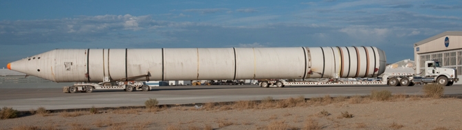 Mounted on special lowboy trailer dollies, one of the two space shuttle solid rocket boosters is hauled up the ramp from Rogers Dry Lake after arrival at NASA Dryden.