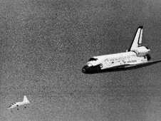 The Space Shuttle Columbia glides down over Rogers Dry Lake as it heads for a landing at Edwards Air Force Base at the conclusion of its first orbital mission on April 14, 1981.