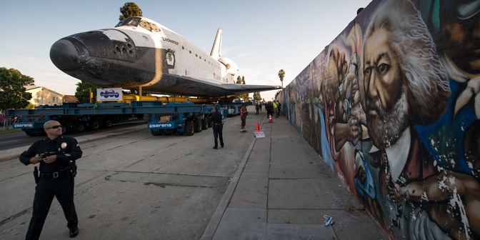 Space shuttle Endeavour is maneuvered past a mural on Crenshaw Boulevard on its way to its new home at the California Science Center in Los Angeles on Saturday, Oct. 13, 2012. Beginning Oct. 30, the shuttle will be on display in CSC's Samuel Oschin Space Shuttle Endeavour Display Pavilion.