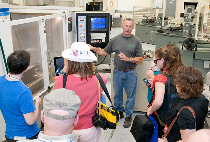 Dryden senior machinist Keith Day describes the functions of a vertical milling center in the center's experimental fabrication shop to followers of NASA's social media accounts during the NASA Social at Dryden.
