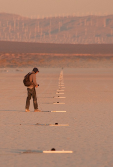 A FaINT project researcher adjusts one of the microphones in a linear array nearly 1 1/2 miles long laid out by the project team to record and measure sonic booms.