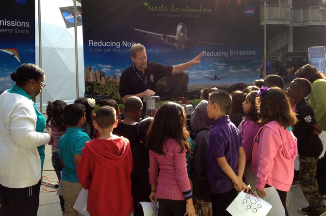 A group of students and their teachers listen intently as Kevin Rohrer of NASA's Dryden Flight Research Center explains flight principles by the NASA Aeronautics exhibit at the NASA SpaceFest at the California Science Center in Los Angeles.