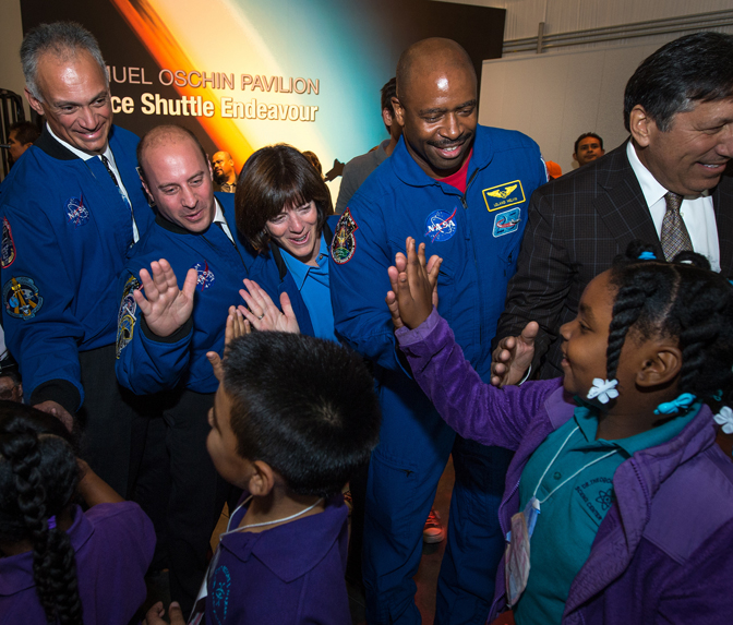 Present and former NASA Astronauts give high fives to school children as they enter the science center's Samuel Oschin Pavilion on Tuesday, Oct. 30, 2012.