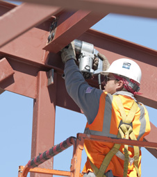 A steelworker bolts girders in place on the structural steel framework of Dryden's new Facilities Support Center.