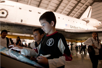 Brandon Cruz, left, and Joseph Alvarez of Downtown Value School in Los Angeles look at a Space Shuttle Endeavour display.
