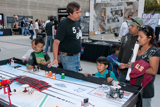 Dryden's Tom Horn talks to a family about the robotics program, which includes a Lego League for younger students.