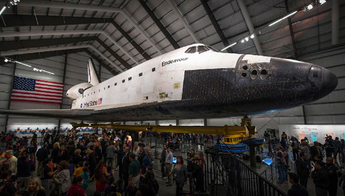Space Shuttle Endeavour, mounted atop its strongback transporter frame on seismic isolator pedestals, is shown in the Samuel Oschin Pavilion at the California Science Center in Los Angeles during the exhibit's grand opening ceremonies.
