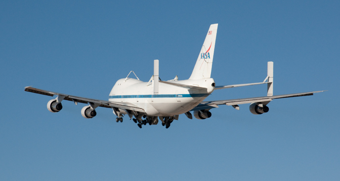 NASA's modified Boeing 747 Space Shuttle Carrier Aircraft (SCA) No. 905 retracts its landing gear as it climbs into the clear blue sky after its last liftoff from Edwards Air Force Base.