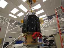 Spacecraft technicians in a clean room at NASA's Ames Research Center, Moffett Field, Calif., lift NASA's LADEE observatory off of its mount to move it to a shipping container for transport.