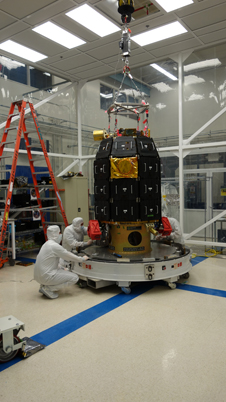 Spacecraft technicians in a clean room at NASA's Ames Research Center, Moffett Field, Calif., set the LADEE observatory down onto the shipping container base and fasten in place.