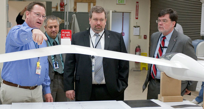 NASA Dryden engineer and project manager Jerry Budd shows off the 1/3-scale Twin Ventus glider center section that would be used to flight validate the aerodynamics of his Towed Glider Air-Launch concept to NASA chief technologist Mason Peck and deputy chief technologist Jim Adams.